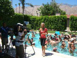 TV reporter looking hot and uncomfortable and hoping her make-up doesn't melt when she could have been skinny dipping.
